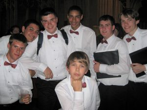 A group of young men in choral uniforms pose for a picture